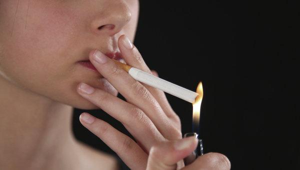 Женщина поджигает сигарету