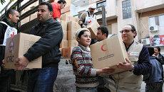 Добровольцы Сирийского Арабского Красного Полумесяца и местные жители разгружают продовольственную помощь, архивное фото