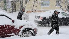 Жители Мурманска на одной из улиц города во время обильного снегопада