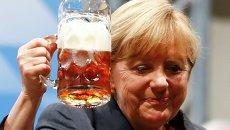 Канцлер Германии Ангела Меркель пьет пиво во время предвыборной встречи