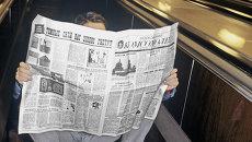 Пассажир московского метро читает газету, сидя на ступенях движущегося эскалатора на станции Фрунзенская.