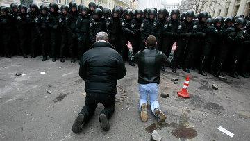 Люди стоят на коленях перед милицией во время митинга сторонников евроинтеграции в Киеве