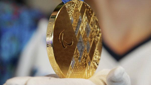 Девушка демонстрирует золотую медаль Паралимпиады-2014. Архивное фото