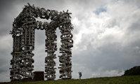 Посетитель у объекта Белые ворота работы художника Николая Полисского на международном фестивале ландшафтных объектов в Никола-Ленивце Калужской области